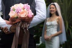 Governi la tenuta del mazzo variopinto di nozze nel suo di nuovo alla sposa di sorpresa, mazzo del primo piano degli ornamenti fotografie stock libere da diritti