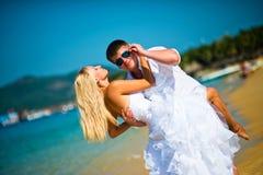 Governi la tenuta della sua sposa sulla spiaggia contro il mare e regola i suoi occhiali da sole immagini stock libere da diritti