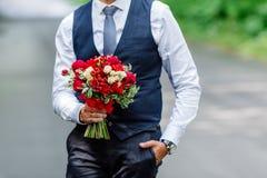 Governi la tenuta in mani delicate, il mazzo nuziale costoso e d'avanguardia di nozze dei fiori in marsala e colorsry rosso alleg fotografie stock