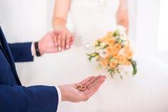 Governi le fedi nuziali della tenuta sulla palma, lo sposo in un vestito blu, le fedi nuziali della tenuta dello sposo, la mano d Immagini Stock Libere da Diritti