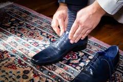 Governi le scarpe d'uso sul giorno delle nozze, legante i pizzi Immagini Stock