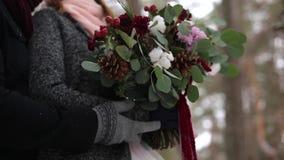 Governi viene alla sposa, abbracci e la baciano dalla parte posteriore nell'abetaia dell'inverno della neve durante le precipitaz video d archivio