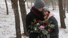 Governi viene alla sposa, abbracci e la baciano dalla parte posteriore nell'abetaia dell'inverno della neve durante le precipitaz stock footage