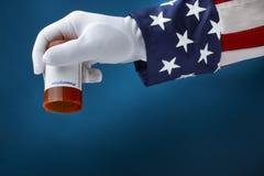 Government Prescription Drug Plan. Close up shot of Uncle Sam holding empty bottle of  prescription drugs Stock Photos
