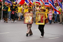 Government protests in Bangkok Thailand. A march with two protesters carrying pictures of the king and queen royalty free stock photography