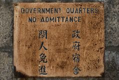 `Government quarters, no admittance` rusty sign in English and Chinese. royalty free stock image