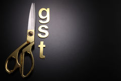 Government service tax. Scissors and word of GST on black background royalty free stock image