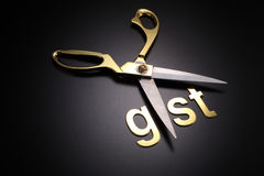 Government service tax. Scissors and word of GST on black background stock photos