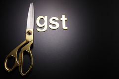 Government service tax. Scissors and word of GST on black background royalty free stock images