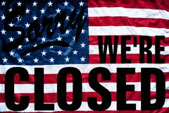 Government shutdown symbolism sorry we`re closed sign. Government shutdown represented by a sorry we`re closed sign outline with american flag background Stock Photos