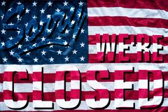 Government shutdown symbolism sorry we`re closed sign. Government shutdown represented by a sorry we`re closed sign outline with american flag background Stock Photo