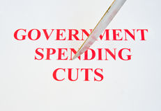 Government spending cuts. An image of a sharp knife cutting across the text ' government spending cuts ' against a plain bright background. It is an abstract stock photography