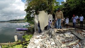 Government workers demolishing illegal structures on lake shore. San Pablo City, Laguna, Philippines - July 6, 2017: Government workers demolishing illegally stock footage