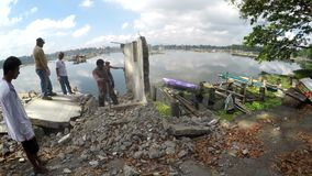Government workers demolishing illegal structures on lake shore. San Pablo City, Laguna, Philippines - July 6, 2017: Government workers demolishing illegally stock video footage