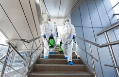 Government workers in protective suits making disinfection of stairs