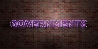 GOVERNMENTS - fluorescent Neon tube Sign on brickwork - Front view - 3D rendered royalty free stock picture Royalty Free Stock Photo