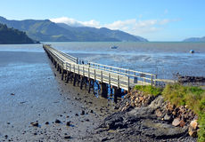 The Governors Bay Jetty at Low Tide. In Winter. Lyttleton in the background Stock Image