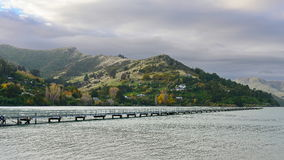 Governors Bay jetty and Port Hills in the background in Christchurch Royalty Free Stock Images