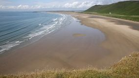 The Gower Wales Rhossili beach with waves breaking on the sand stock footage