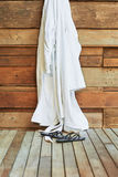 Gown or robe hanging in a Spa with sandals Royalty Free Stock Images