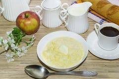 Gozó de la mesa de desayuno con las gachas de avena del maíz, una taza de café y Apple Foto de archivo libre de regalías
