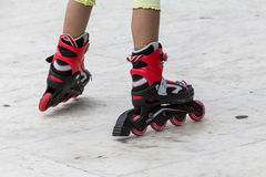 Gozando del patinaje sobre ruedas rollerblading en patines en línea diviértase adentro Imagenes de archivo