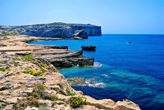 Gozo coastline, Fungus Rock. View of the Gozo coastline, in Maltese archipelago. Fungus Rock is a small, rocky islet in the deep and clear waters of Dwerja Bay Stock Photos