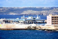Ferry terminal for Gozo at Paradise Bay, Malta. Gozo ferry in the ferry terminal with Gozo and Comino to the rear, Paradise Bay, Malta, Europe Stock Images