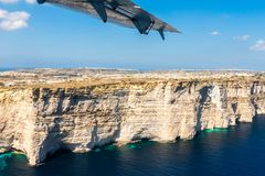 Gozo island from above, under the wing of a small plane. Aerial view of Gozo, Malta. Rotunda of Xewkija or Casal XeuchiaЧ. royalty free stock photography