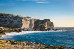 Gozo Island cliffs, Malta. Gozo Island cliffs with Fungus Rock small islet during the spring storm. Dwejra, Maltese archipelago Royalty Free Stock Image