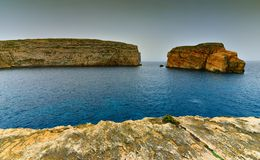 Gozo island cliffs, Malta seaside landscape. Malta seaside landscape  and Fungus Rock, known as the General`s Rock, at the entrance to the Dwajra Bay, on the Stock Photos