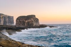 Gozo Island cliffs at sunset, Malta. Gozo Island cliffs with Fungus Rock small islet during the spring storm. Dwejra, Maltese archipelago Royalty Free Stock Photos
