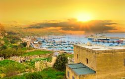 Gozo island in colorful light at sunrise, in Malta. Beautiful panorama of Gozo island in colorful light at sunrise, in Malta, Europe. Travel to the most Royalty Free Stock Photos