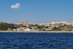 Gozo Island, Malta Gozo port landscape. Gozo Channel Line Ferry at port with background view of city buildings and Ghajnsielem Parish Church Royalty Free Stock Image