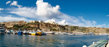 Gozo Island View. GOZO, MALTA - OCTOBER 31, 2015 : General seascape view of Gozo island in Malta with boats around, on cloudy blue sky background Royalty Free Stock Photography