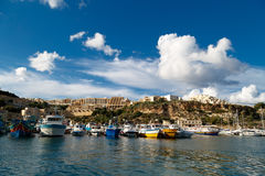 Gozo Island View. GOZO, MALTA - OCTOBER 31, 2015 : General seascape view of Gozo island in Malta with boats around, on cloudy blue sky background Royalty Free Stock Photos