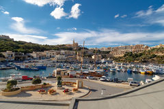 Gozo Island View. GOZO, MALTA - OCTOBER 31, 2015 : General seascape view of Gozo island in Malta with boats around, on cloudy blue sky background Stock Image