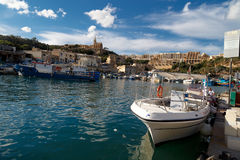 Gozo Island View. GOZO, MALTA - OCTOBER 31, 2015 : General seascape view of Gozo island in Malta with boats around, on cloudy blue sky background Royalty Free Stock Photo
