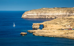 Gozo, Malta - The Azure Window and Dwejra bay. On a beautiful summer day with sail boat and clear blue sky Royalty Free Stock Image