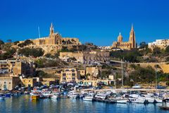 Gozo, Malta - The harbour of Mgarr with view of church Our Lady of Lourdes on top. Of the hill on a bright sunny summer day with blue sky Stock Image
