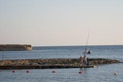 GOZO, MALTA - Juli 04, 2019: Twee vissers die vissen vangen bij de zeekust stock afbeeldingen