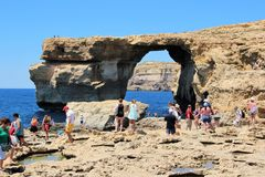 Gozo, Malta, July 2016. Numerous tourists on the rocky site near the famous Blue Window. royalty free stock photography