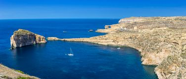 Gozo, Malta - Panoramic skyline view of Dwejra bay with Fungus R. Ock, Azure Window and sailboat on a nice hot summer day Royalty Free Stock Photos