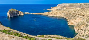Gozo, Malta - Panoramic skyline view of Dwejra bay with Fungus R. Ock, Azure Window and sailboat on a nice hot summer day Stock Photo