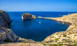Gozo, Malta - Panoramic skyline view of Dwejra bay with Fungus R. Ock, Azure Window and sailboat on a nice hot summer day Royalty Free Stock Photography