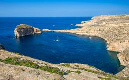 Gozo, Malta - Panoramic skyline view of Dwejra bay with Fungus Rock. Azure Window and sailboat on a nice hot summer day Stock Images