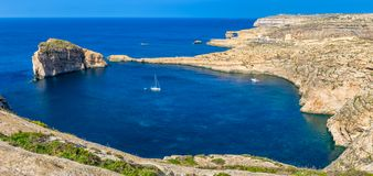 Gozo, Malta - Panoramic skyline view of Dwejra bay with Fungus Rock. Azure Window and sailboat on a nice hot summer day Stock Photo
