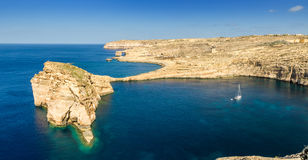 Gozo, Malta - Panoramic view of the beautiful Fungus rock. With the Azure Window and sail boat at Dwejra bay on a beautiful summer day with clear blue sky Royalty Free Stock Image