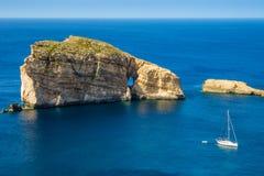 Gozo, Malta - roca fungosa asombrosa en la bahía de Dwejra con el velero Imagenes de archivo