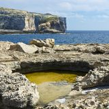 Rugged coastline of island of Gozo. Gozo is a small island of the Maltese archipelago in the Mediterranean Sea.  Rugged coastline delineated by sheer limestone Stock Photography